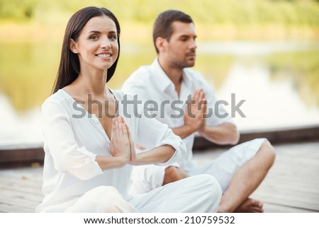 Finding peace and harmony inside themselves. Beautiful young couple in white clothing meditating outdoors together and keeping eyes closed - stock photo