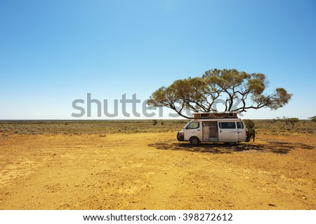 Finding shade under a lone tree while traveling in the Australian outback in a campervan.