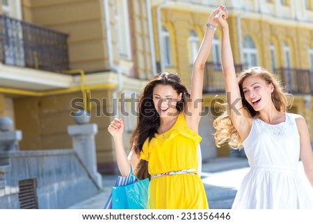 Finding the best shopping offer. Two young and pretty girls are going shopping with shopping bags. They are smiling and raising hands up - stock photo