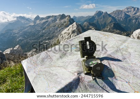 Finding your way with a compass and a map on the top of the mountain Rombon, Slovenia - stock photo