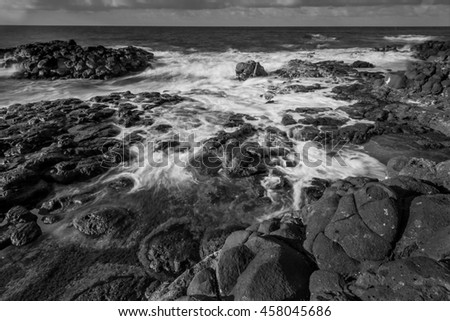 Fine art black and white image of ocean waves at sunset along the Queens Bath area of Kauai, Hawaii