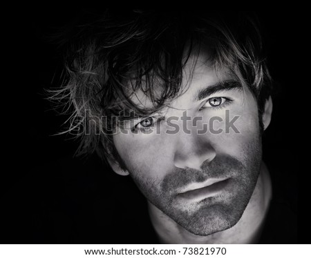 Fine art close-up black and white portrait of beautiful young man's face against black background