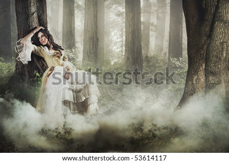 Fine art photo of a gorgeous lady in a mysterious foggy forest - stock photo