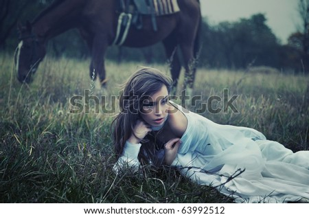 Fine art photo of a young beauty on the grass - stock photo