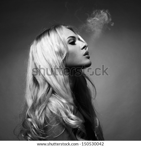 Fine art portrait of a beautiful lady smokes - stock photo