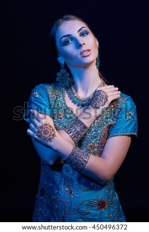Fine art portrait of beautiful fashion Indian woman with oriental dress, accessories- earrings, bracelets and rings and mehndi henna tattoos. - stock photo