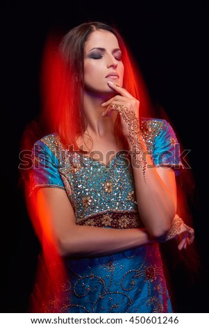 Fine art portrait of beautiful fashion Indian woman with oriental dress, accessories- earrings, bracelets and rings and mehndi henna tattoos. Mixed lighting photography. - stock photo