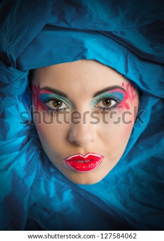 Fine art portrait of woman with colorful makeup in blue turban (looking at camera)