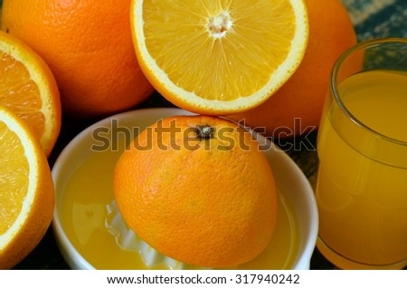 Fine art still life with orange juice and porcelain juicer on wooden table - stock photo