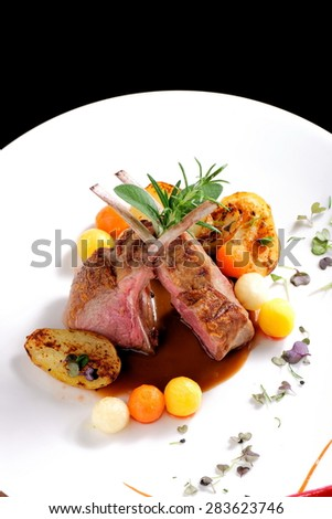 Fine dining, roasted Lamb chops with potato, rosemary and vegetable sauce - stock photo