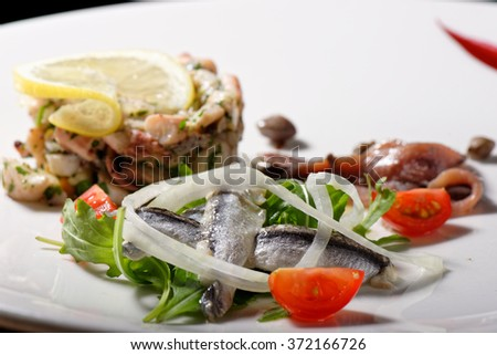 Fine dining seafood appetizer with Anchovies and octopus salad - stock photo