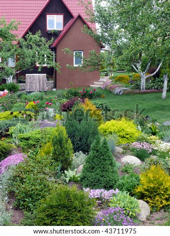 Fine flowers and ornamental shrubs near an accurate rural cottage. - stock photo