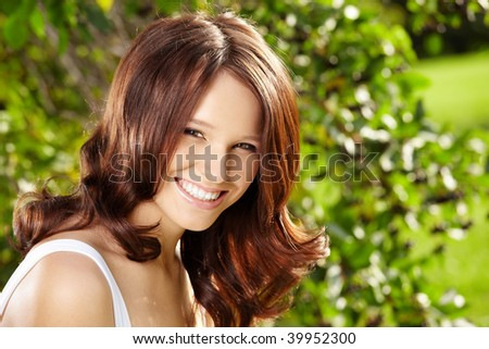 Fine girl with a charming hairdress against a summer garden - stock photo