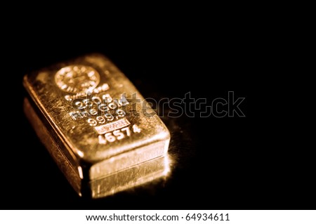 fine gold ingot isolated on a black background.  shallow depth of field.