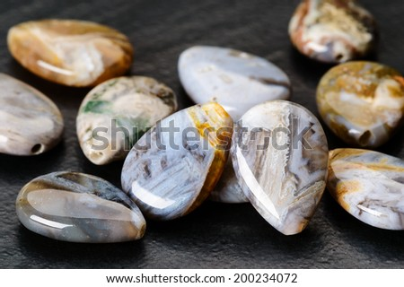 Fine lot of teardrop shaped agate beads with lovely patterns on black stone. - stock photo