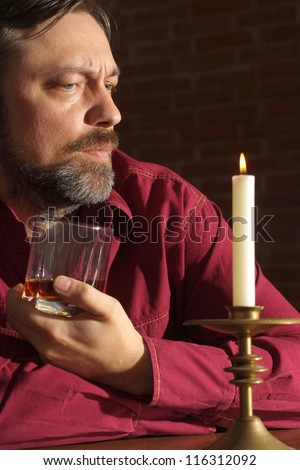 Fine man sits quietly at his home at the table - stock photo