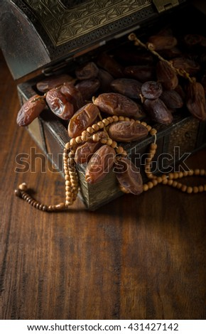 Fine quality Arabian dates stored in antique wooden trunk with Islamic prayer beads. Ramadan food and objects. - stock photo