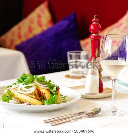 Fine restaurant dinner table place setting: napkin, wineglass - stock photo