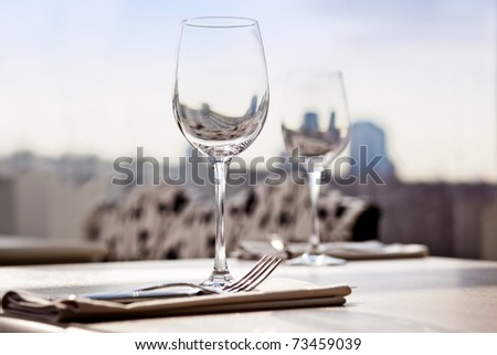 Fine restaurant dinner table place setting: napkin & wineglass - stock photo
