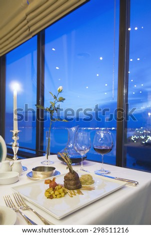 Fine restaurant dinner table place setting: napkin, wineglass, plate, beef and flowers - stock photo