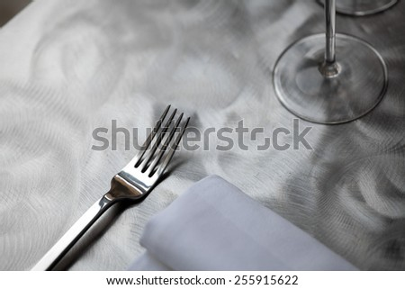Fine restaurant dinner table place setting with napkin and wineglass - stock photo