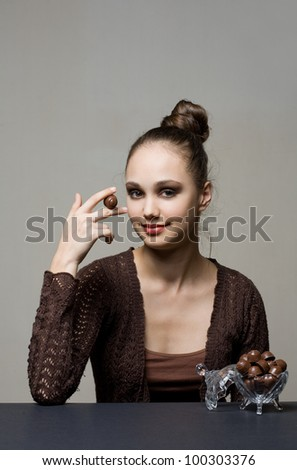 Finest chocolate, gorgeous young brunette with tasty pralines. - stock photo