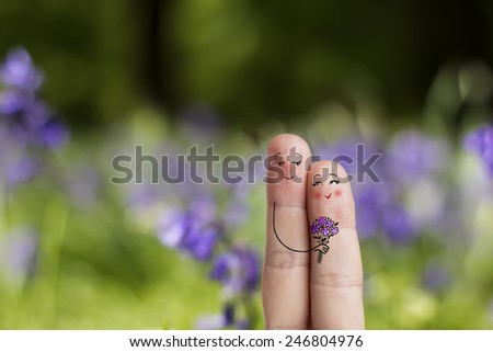 Finger art. Lovers is embracing and holding bouquet Happy Valentine's Day and 8 March love theme series. Painted fingers There are path in image. You can easily cut out fingers from the background.  - stock photo