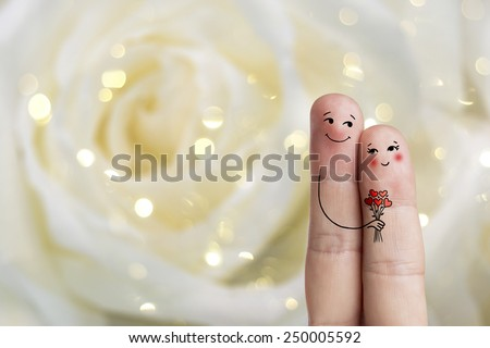 Finger art of a Happy couple. Man is giving bouquet. Stock Image Happy Valentine's Day and 8 March creative love series.  There is path  in image. You can easily cut out fingers from the background. - stock photo
