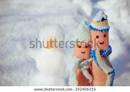 Finger art of a Happy couple on the background of snow and the snowman. Toned image.  - stock photo