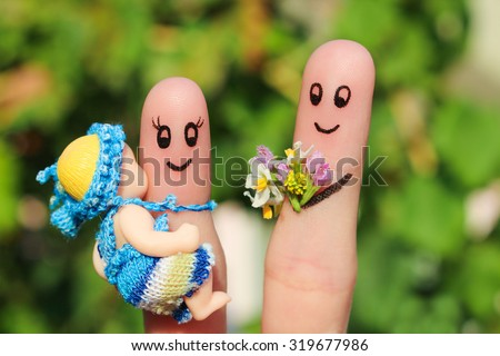 Finger art of a Happy family holding a small child. Concept of husband giving flowers to his wife for birth of child.  - stock photo