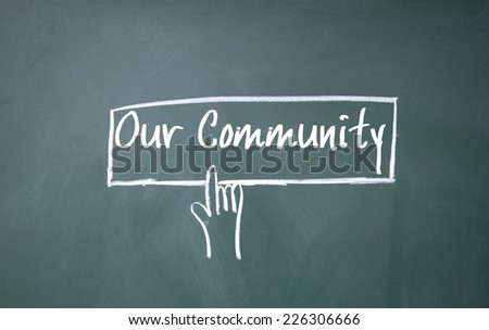 finger click our community symbol on blackboard - stock photo