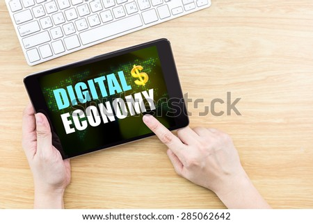 Finger click screen with Digiral Economy word with keyboard on wooden table,,Business concept - stock photo