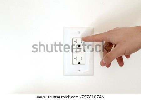 Finger dangerously close to electrical socket.  Risk of electrocution and electric shock.