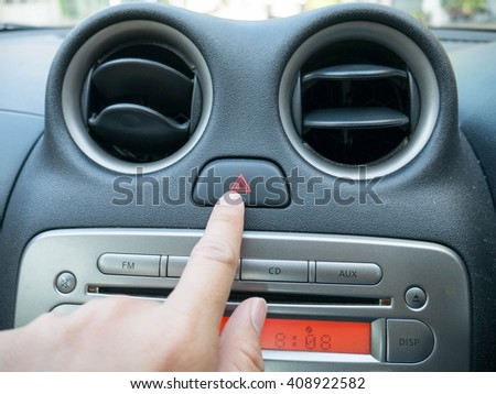 Finger hitting car emergency light botton - stock photo