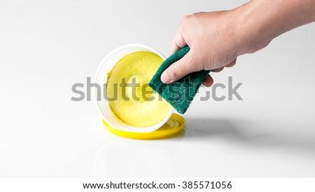 Finger holding dishwasher sponge nearby dishwashing paste. Isolated on empty background. Slightly de-focused and close-up shot. Copy space. - stock photo