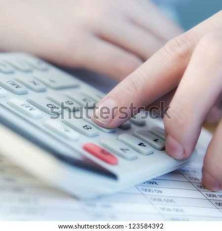 Finger is pressing calculator button on chart - stock photo