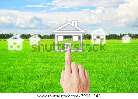 Finger is pressing on the house on meadow - stock photo