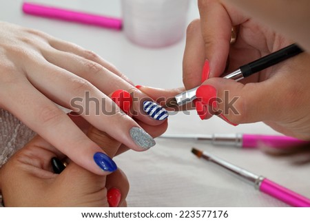 Finger nail treatment, painting lines with brush and lacquer - stock photo