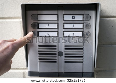 Finger on the home intercom - stock photo