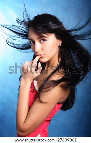 Finger on the lips of a model. Hair motion - stock photo