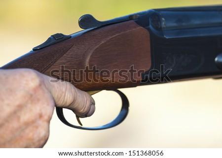 Finger on the trigger of a shotgun - stock photo