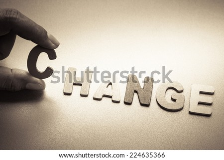 Finger pick a wood letters of Change word - stock photo