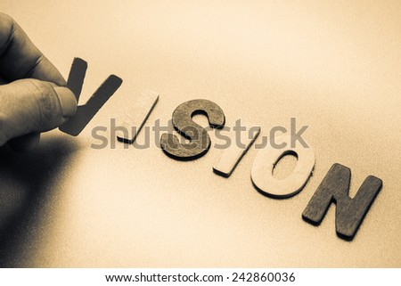 Finger pick a wood letters of Vision word - stock photo