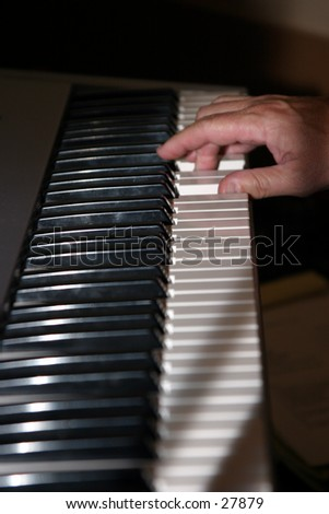 finger playing a keyboard making music