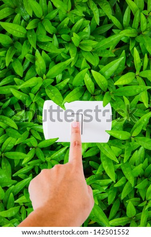 finger pointing at switch with leaf background - save energy concept - stock photo