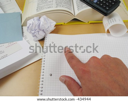 Finger pointing on blank paper with calculations and bills in the background