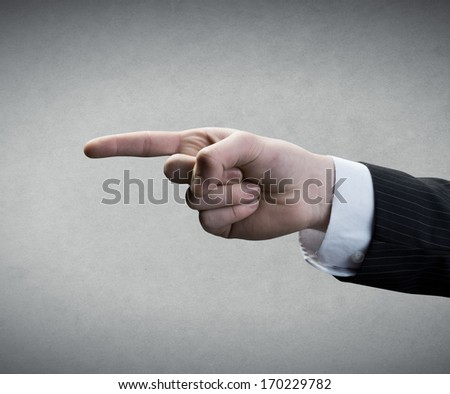 Finger pointing on gray background. - stock photo