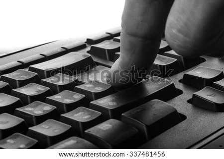 finger presses enter in an old and dirty keyboard - stock photo
