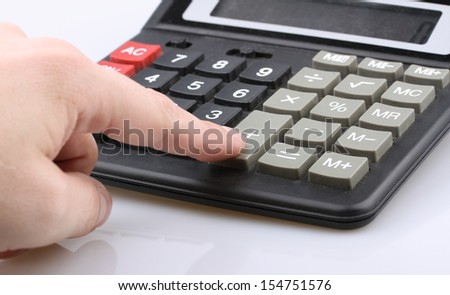 finger presses the button on the calculator plus