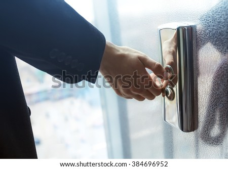 finger presses the elevator button. Red button. bluet light. businessman is a lift. high floor. hand reaches for the button of the elevator call.